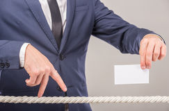 Hands. Close-up of business man's hand walking with fingers on rope and holding business card in another hand Royalty Free Stock Photography