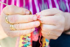 Hands close-up of an old woman knitting on knitting needles, using colorful wool royalty free stock image
