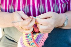 View of hands close-up of an old lady knitting on knitting needles, using colorful wool royalty free stock image
