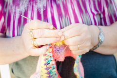 Close up of Hands of an old lady knitting on knitting needles, using colorful wool stock image