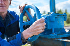 Hands close-up of senior manual worker turning cut-off valve Stock Photos
