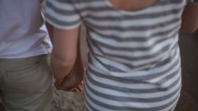 Hands close-up, view from the back. young man and woman walking along the edge of the water at sunset stock video