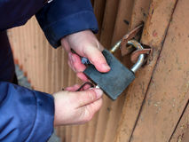 Hands closed padlock key on the gate stock photo
