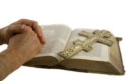 Hands closed in prayer and cross. On an open bible isolated white Stock Image