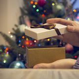 Hands closing a gift box on a wooden table against decorated Christmas tree stock photo