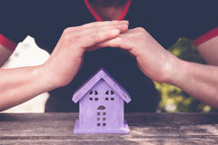 Hands closing toy house of lavender color,. As a symbol of safety royalty free stock image