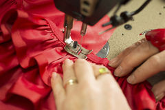 Hands on Cloth Fastened Through a Sewing Machine Royalty Free Stock Photography
