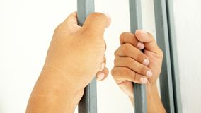 Hands clutching bars. Close up royalty free stock photo