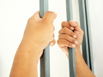 Hands clutching bars Royalty Free Stock Photos