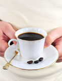 Hands with coffee. Coffee in white porcelain cup, held by man's hands Royalty Free Stock Images