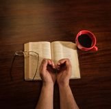 Hands With Coffee and Bible. A man's two hands open in prayer, forming a heart shape, an open bible, glasses, and cup of coffee on a dark wooden table Royalty Free Stock Photo