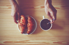 Hands with coffee cup and croissants Stock Image