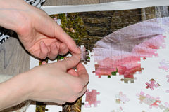 Hands collect puzzle. Hands collect beautiful puzzle on wooden background Stock Photos