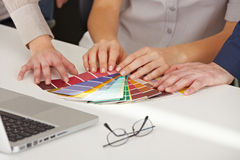 Hands with color pattern samples. Many hands with different color pattern samples on the office table royalty free stock photos