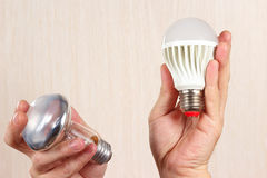 Hands compared incandescent bulb and ecofriendly led lamp. On a light wood background royalty free stock image