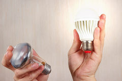 Hands compared incandescent bulb and glowing ecofriendly led lamp. On a light wood background stock photos