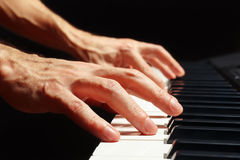 Hands of composer play the keys of the piano on black background close up Stock Image