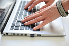 Hands on computer. Close up of female hands on a computer laptop Stock Photos