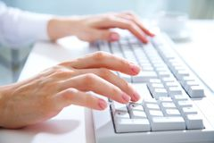 Hands on computer keyboard. Female hands typing on white computer keyboard Stock Photos