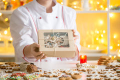 Hands of confectioner showing a box with gingerbread cookies. Hands of professional smiling confectioner showing a box with beautifully decorated gingerbread Stock Images