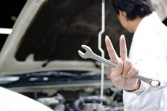 Hands of confident young mechanic holding wrench and raising two fingers up it is shows fight with job against car in open hood at. The repair garage Royalty Free Stock Photo