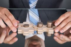 Hands connecting puzzle pices with coins Stock Photography