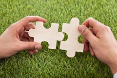 Hands connecting two puzzle pieces Royalty Free Stock Photos
