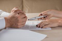 Hands of contractual parties, a woman and a man, signing a contract Royalty Free Stock Images