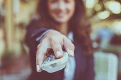 Hands with controller in focus. Young smiling woman with remote Royalty Free Stock Photos