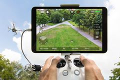 Hands controlling drone filming park against cloudy sky. Cropped image of hands controlling drone filming park seen on digital tablet stock photos