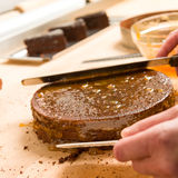 Hands of cook in action spreading cake Royalty Free Stock Photography