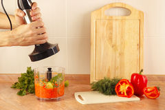 Hands cook are going to shred vegetables in blender Stock Photos