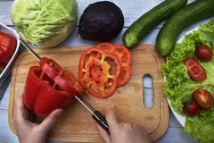 Housewife slicing sweet pepper for salad Royalty Free Stock Images