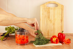 Hands cook put chopped fresh herbs in blender Royalty Free Stock Photos
