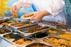 Hands of cook putting in plate vegetable ragout Stock Image