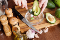 Hands cooking with avocado. At table in home kitchen Royalty Free Stock Images