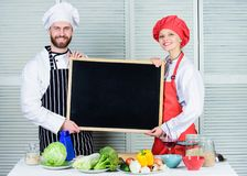 Hands on cooking class. Couple of man and woman holding empty blackboard in cooking school. Chef and cook helper royalty free stock images