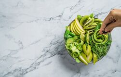 Free Hands Cooking Fresh Summer Salad With Avocado, Kiwi, Apple, Cucumber, Pear, Micro Greens, Lime And Sesame On Light Marble Royalty Free Stock Photography - 172287727
