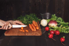 Hands cooking healthy meal in the kitchen, cutting vegetables on the wooden table Royalty Free Stock Images