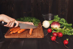 Hands cooking healthy meal in the kitchen, cutting vegetables on the wooden table Stock Photography