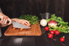 Hands cooking healthy meal in the kitchen, cutting vegetables on the wooden table Stock Photos