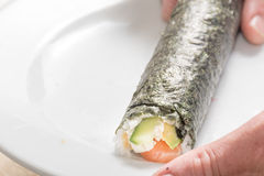 Hands cooking sushi roll with rice, salmon and Royalty Free Stock Photos