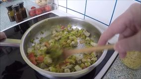 Hands cooking vegetable ragout in pan in kitchen stock video