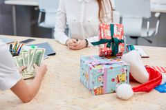 Hands counting the money while the consultant is waiting on the table with a pile of gifts Stock Images