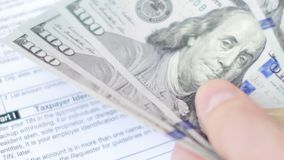 Hands counting dollars banknotes above tax form. 4K UltraHD video. Footage stock footage