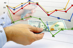 Hands counting money with financial graph. Businessmans' hands counting money and financial graph - Financial concept Stock Image