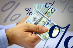 Hands counting money with percent signs floating around Royalty Free Stock Photos