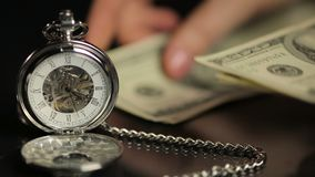 Hands counting money, person calculating savings, time flies on pocket watch. Stock footage stock video footage