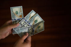 Hands counting money. Hands counting some notes of one hundred US dollars Stock Photography