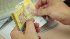 Hands Counting Ukrainian Hryvnia. Male hands are counting Ukrainian banknotes. Then the hand pours coins from purse stock video